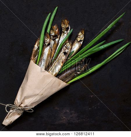 Smoked capelin with green onions in paper cornet on an old iron background. Top view