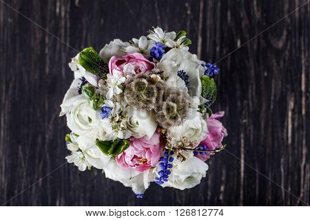 Bouquet from pink tulips violet grape hyacinths white anemones violet veronica and white buttercup with violet ribbon on black old wood from the top