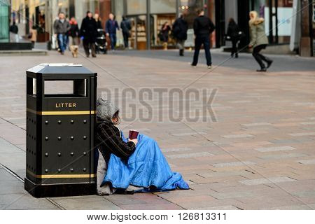 An unidentifed person begging on a street in Glasgow Scotland.