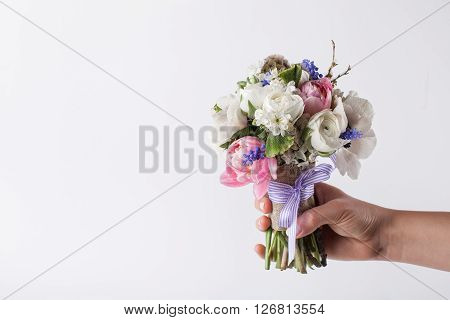 One hand is giving spring bouquet from pink tulips violet grape hyacinths white anemones violet veronica and white buttercup with violet ribbon on the white background