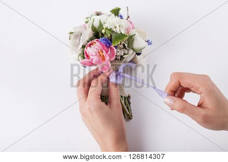 Two hands are making a bow from a violet ribbon in beautiful spring bouquet from pink tulips violet grape hyacinths white anemones violet veronica and white buttercups on white background