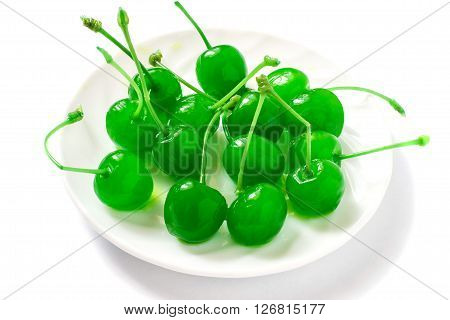 Green maraschino cherry on a plate on a white background