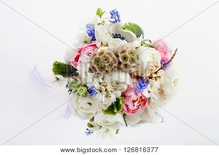 Bouquet from pink tulips violet grape hyacinths white anemones violet veronica and white buttercup with violet ribbon on white background from the top