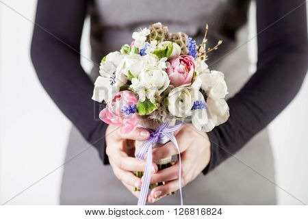 Woman in grey dress and black shirt is giving spring bouquet from pink tulips violet grape hyacinths white anemones violet veronica and white buttercup with violet ribbon