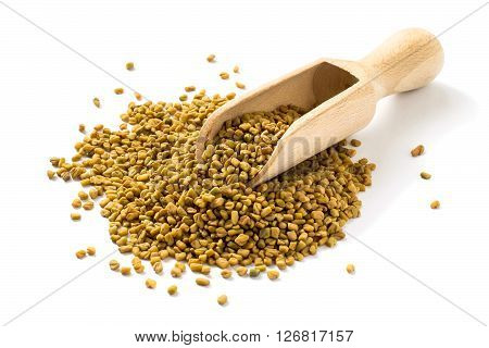 Fenugreek seeds in a wooden scoop on a white background