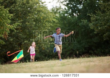 Girl and boy flying a kite in summer