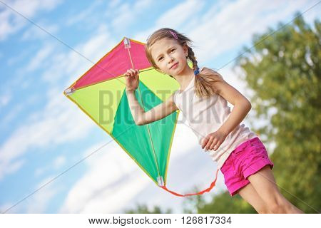 Girl with a colorful kite  in nature