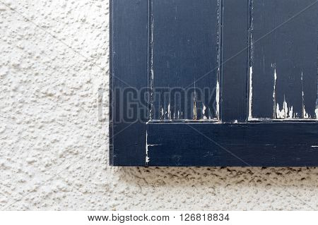 Old dark blue rough vintage window shutter with peeling paint on white wall copy space background