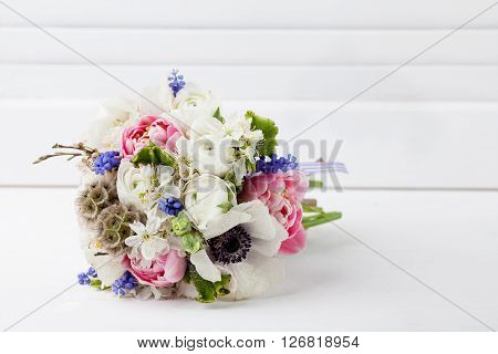 Bouquet from pink tulips violet grape hyacinths white anemones violet veronica and white buttercup with violet ribbon lying on the floor with white wooden shutter background