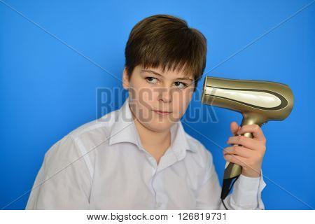 Boy teenager dries hair the hair dryer