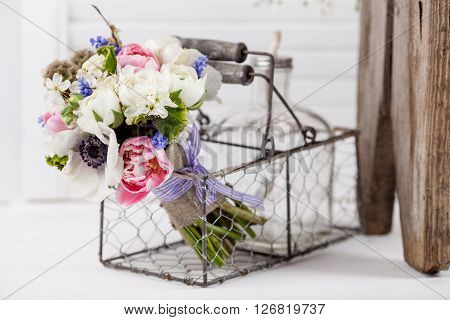 Bouquet from pink tulips violet grape hyacinths white anemones violet veronica and white buttercup with violet ribbon lying in the metal rustic basket with glass bottle on white shutter background with old wooden bench