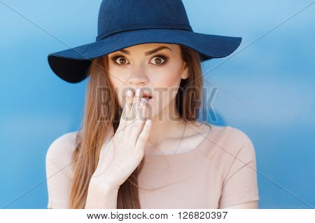 Young beautiful woman brunette with long straight hair and brown eyes,dressed in a beige blouse, wearing a faded blue hat with a large brim, poses for photographer during the summer in the open air, covering your mouth in surprise