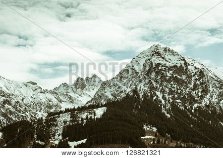 Snowcapped mountain peaks with clouds in vintage look