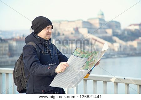 Man tourist. Young man with map in hand. He is looking from the bridge to the other side of Budapest. Winter holidays in Budapest Hungary. Map city tour travel vacation holiday - concept.