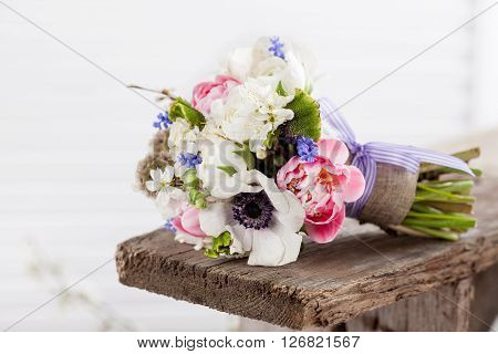 Bouquet from pink tulips violet grape hyacinths white anemones violet veronica and white buttercup with violet ribbon lying on the old wooden bench with white shutter background