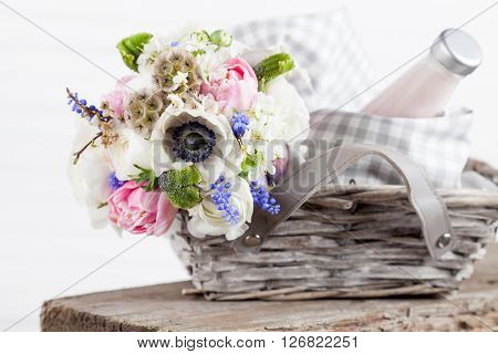 Bouquet from pink tulips violet grape hyacinths white anemones violet veronica and white buttercup with violet ribbon lying in the picnic basket with milkshake in the bottle and sweets in the jar with white background and the old wooden bench