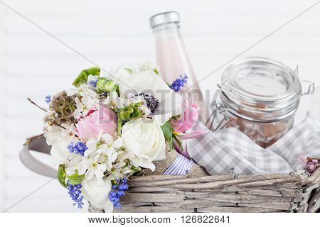 Bouquet from pink tulips violet grape hyacinths white anemones violet veronica and white buttercup with violet ribbon lying in the picnic basket with milkshake in the bottle and sweets in the jar with white background