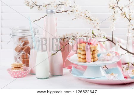 Four bottles of milkshakes three with straws and glass of milk and plates with cookies and biscuits tied with pink ribbon jar of candies and cloth with spring blossom plum tree and little flowers on white wood and shutter background