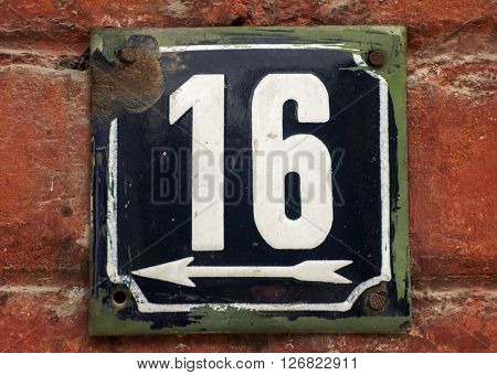 Weathered grunge square metal enameled plate of number of street address with number 16 closeup