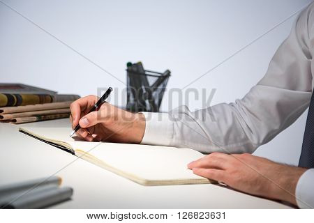 Sideview of businessman hands writing in journal on office table