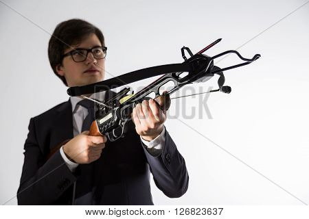 Businessman with crossbow in hands looking into the distance on light background