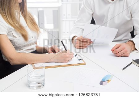 Businessman and woman discussing business report at office desk