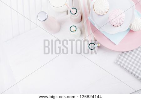 Four bottles of milkshakes three with straws and glass of milk and plates with pink and white meringues and cloth on white wooden shutter from the top