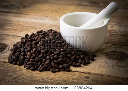 Coffee beans on rustic wooden background and white mortar