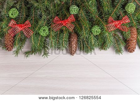 Decor winter holidays fir branches with cones with green clouds of twigs and red bow