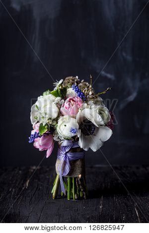 Bouquet from pink tulips violet grape hyacinths white anemones violet veronica and white buttercup with violet ribbon standing on black rought wood with blackboard in the background
