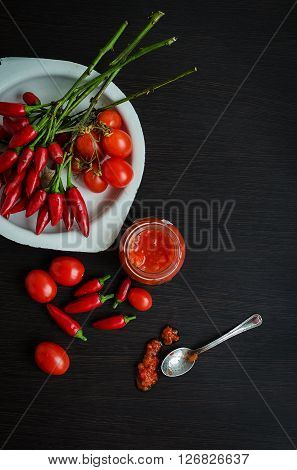 Glass jar of homemade tomato sauce with fresh ingredients on dark wooden background. Natural homemade sauce of tomatoes, peppers and vegetables. Fresh Homemade Salsa Dip. Chilli jam. Top view.