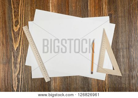 Triangle centimeter ruler, simple centimeter ruler, pencil and white paper on laminate. Work place of constructor in top view.