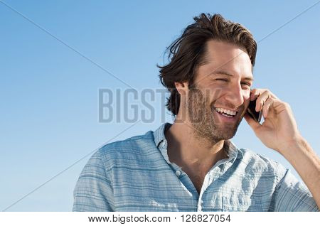 Handsome young man smiling and talking on phone. Cheerful young man in a joyful conversation at telephone with copy space. Portrait of happy joyous man using smart phone outdoor.