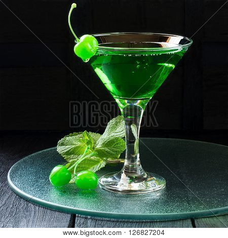 Green cocktail with maraschino cherry in a martini glass on a glass tray and dark background. Square image