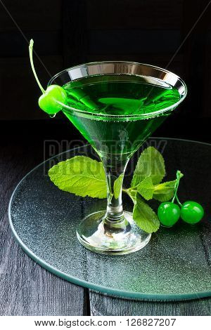 Green cocktail with maraschino cherry in a martini glass on a glass tray and dark background