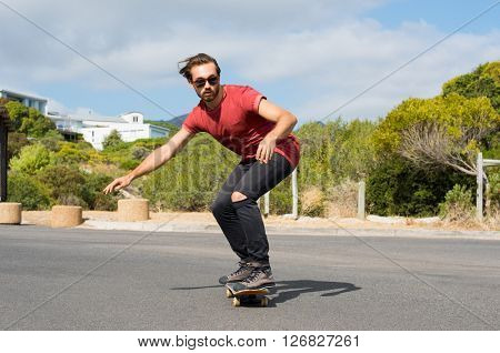 Young man riding on a skate in the city street. Cool skater doing a stunt on his skateboard. Cool street skateboarder in a urban scene.