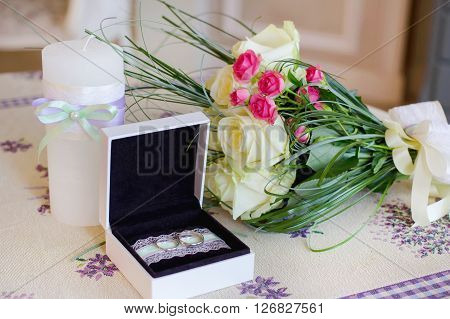 Gold Wedding rings in a box and Bouquet roses. Holiday background for Valentines day or wedding day. Blurred background image.