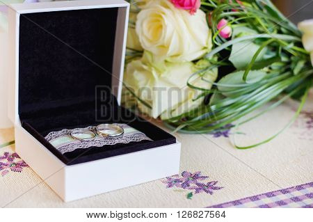 Gold Wedding rings in a box and Bouquet roses. Holiday background for wedding day. Blurred background image.