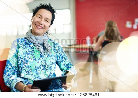 Casual portrait of a mature business woman using technology in a bright and sunny startup with the team in the background