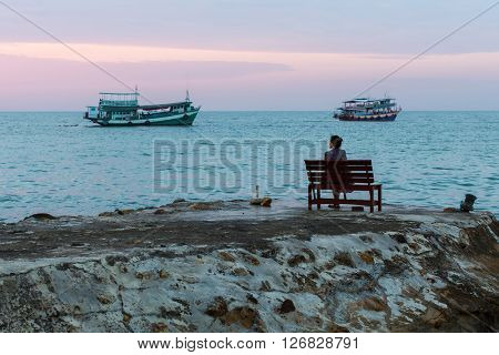 Lonely woman sitting on a bench near the sea in the evening.