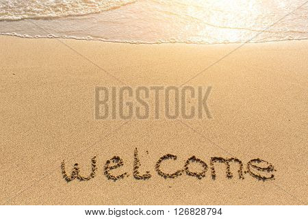 Welcome - word drawn on the sand beach with the soft wave.
