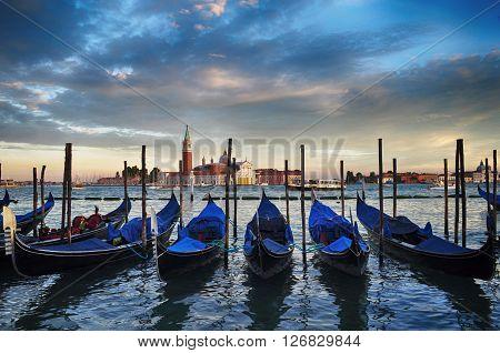 Sunset in Venice. Gondolas moored on Grand Canal and San Giorgio Maggiore church in the background. Venice, Italy, Europe.
