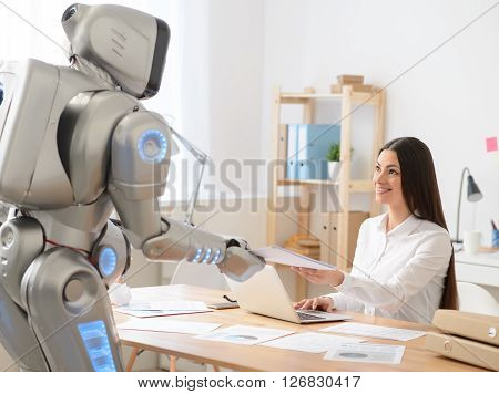 Nice colleague. Cheerful smiling beautiful girl sitting at the table and giving papers to the robot who is standing nearby