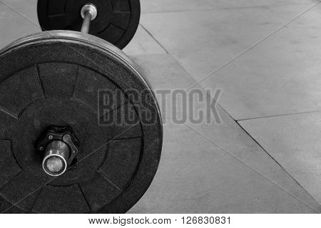 Barbell with weight plates on a gym floor, in black and white