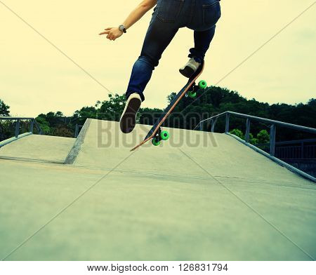 young woman skateboarder skateboarding at skate park ** Note: Soft Focus at 100%, best at smaller sizes