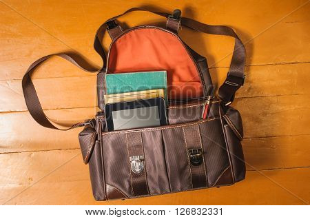 Vintage bag with old books on wood