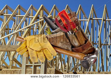 Carpenter tools hammer nails screws level tape measure screwdrivers pliers and hacksaw with wood framed structure in background