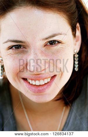 young happy caucasian smiling woman portrait with freckles on face