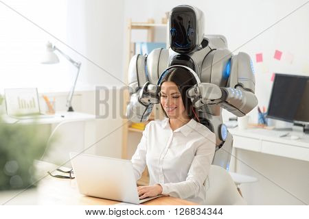 Get some rest. Pleasant pretty smiling woman sitting at the table and working on the laptop while robot wearing headphones on her head