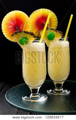 Refreshing pineapple cocktail with coconut in glasses with slices of pineapple green cocktail cherry straws and decoration for glasses in the form of a fan